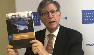 Jose Miguel Vivanco, Americas director at Human Rights Watch, shows journalists a report about Nicaragua at the HRW office in Washington on Wednesday June 19, 2019. (AP Photo/Luis Alonso Lugo)
