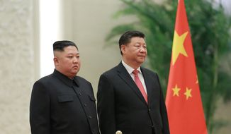 """In this Jan. 8, 2019, file photo provided by the North Korean government, North Korean leader Kim Jong-un, left, and Chinese President Xi Jinping attend a welcome ceremony at the Great Hall of the People in Beijing. Xi said North Korea is taking the """"right direction"""" by politically resolving issues on the Korean Peninsula in a rare op-ed published by a North Korean state newspaper Wednesday, June 19, 2019, a day before Xi visits Pyongyang to meet Kim. (Korean Central News Agency/Korea News Service via AP, File)"""