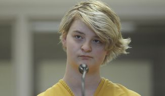 In this Sunday, June 9, 2019 photo, Denali Brehmer, 18, stands at her arraignment in the Anchorage Correctional Center in Anchorage, Alaska.   Brehmer has been charged with first-degree murder in the death of Cynthia Hoffman. . (Bill Roth/Anchorage Daily News via AP)