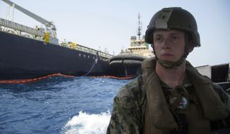 """The damaged Panama-flagged, Japanese owned oil tanker Kokuka Courageous, that the U.S. Navy says was damaged by a limpet mine, is seen behind a U.S. sailor, during a trip organized by the Navy for journalists, off Fujairah, United Arab Emirates, Wednesday, June 19, 2019. The limpet mines used to attack the oil tanker near the Strait of Hormuz bore """"a striking resemblance"""" to similar mines displayed by Iran, a U.S. Navy explosives expert said Wednesday. Iran has denied being involved. (AP Photo/Fay Abuelgasim)"""