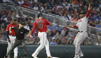 Boston Red Sox's Rafael Devers holds up the ball after he picked off Minnesota Twins' catcher Mitch Garver at third base during the sixth inning of a baseball game Tuesday, June 18, 2019, in Minneapolis. Devers caught the ball from catcher Christian Vazquez. (AP Photo/Stacy Bengs)