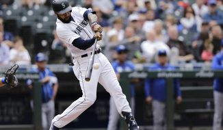 Seattle Mariners' Domingo Santana hits an RBI single against the Kansas City Royals during the fourth inning of a baseball game Wednesday, June 19, 2019, in Seattle. (AP Photo/John Froschauer)