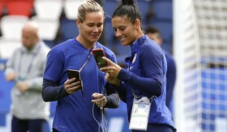 FILE - In this June 15, 2019, file photo, U.S. teammates Ashlyn Harris, left, and Ali Krieger chat during a visit to the Parc des Princes stadium a day before a soccer match against Chile at the Women's World Cup in Paris. Many World Cup teammates have special bonds. The tie that binds U.S. defender Krieger and goalkeeperHarris is likely the strongest at the tournament. They got engaged last year and are planning a December wedding. (AP Photo/Alessandra Tarantino, File)