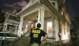 An agent from the Immigration and Customs Enforcement agency keeps watch at the side of a house while other agents from ICE are inside in search of a suspect during a sweep to capture illegal aliens with a criminal record in the Boston area, Tuesday, June 13, 2006, in the Brighton neighborhood of Boston. More than 2,100 illegal immigrants have been arrested since the nationwide raid began May 26. (AP Photo/Michael Dwyer)