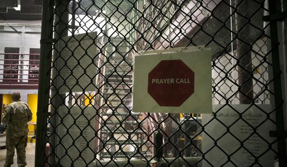This Wednesday, June 6, 2018, photo, reviewed by U.S. military officials, shows a placard announcing prayer call at the maximum security prison at Camp VI, at the Guantanamo Bay U.S. Naval Base, in Guantanamo, Cuba. The detention center opened in January 2002 under then-President George W. Bush as a makeshift place to hold and interrogate people suspected of involvement with al Qaeda and the Taliban. (AP Photo/Ramon Espinosa)