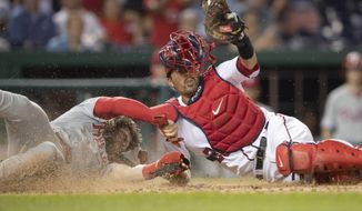 Washington Nationals catcher Kurt Suzuki raises his glove with the ball after tagging out Philadelphia Phillies' Bryce Harper at the home plate during the fourth inning of a baseball game in Washington, Thursday, June 20, 2019. (AP Photo/Manuel Balce Ceneta)
