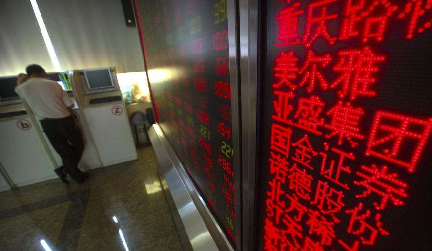 A Chinese investor uses a computer terminal as he monitors stock prices at a brokerage house in Beijing, Thursday, June 20, 2019. (AP Photo/Mark Schiefelbein) ** FILE **