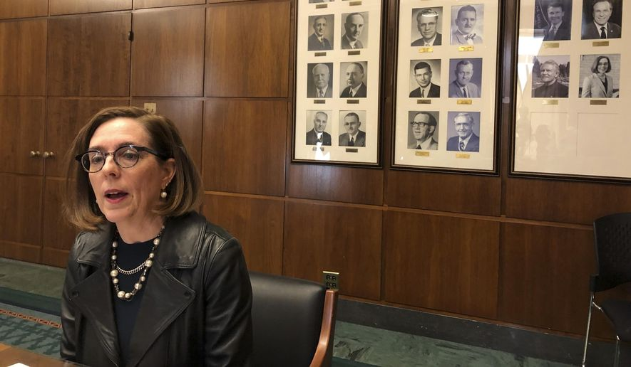 In this Feb. 7, 2019, file photo, Oregon Gov. Kate Brown speaks to reporters in front of pictures of previous state governors in Salem, Ore. Gov. Brown deployed the state police Thursday, June 20, 2019, to try to round up Republican lawmakers who fled the Capitol in an attempt to block a vote on a landmark climate plan. Minority Republicans want the cap and trade proposal aimed at dramatically lowering the state's greenhouse gas emissions by 2050 to be sent to the voters for approval instead of instituted by lawmakers. (AP Photo/Andrew Selsky, File) **FILE**
