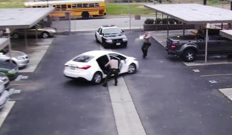 In this June 6, 2019 image from surveillance video provided by the Los Angeles County Sheriff's Department, a Los Angeles County sheriff deputy opens a rear door of a parked vehicle while a fellow office fires his gun at the car, fatally shooting Ryan Twyman. The video shows the reversing car's door striking the deputy before he and the other deputy open fire on the vehicle.  The family of Twyman, who was unarmed during the incident, filed a claim for damages against Los Angeles County. (Los Angeles County Sheriff Department via AP)
