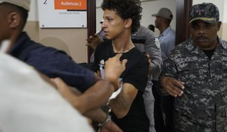 In this June 13, 2019 file photo Rolfy Ferreyra Cruz, center, is taken to court by police in Santo Domingo, Dominican Republic. The suspect in the shooting of former baseball star David Ortiz has been charged with drug and firearm possession in New Jersey. The U.S. attorney's office in Newark announced the indictment Thursday, June 20, 2019 for Rolfy Ferreyra Cruz. (AP Photo/Roberto Guzman, file)