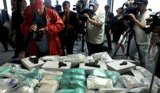 Members of the media take images of guns, drugs and money on display at a press conference, Thursday, June 20, 2019, in Boston. Authorities in Massachusetts have arrested 14 people and seized more than 24 kilograms (53 pounds) of fentanyl, heroin and cocaine in the bust of a major drug trafficking ring.  (Nancy Lane/The Boston Herald via AP)