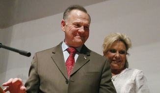 In this Tuesday, Dec. 12, 2017, file photo, Republican Senate candidate Roy Moore walks off the stage with wife Kayla Moore after he spoke to supporters after an election-night watch party at the RSA activity center, in Montgomery, Ala. Moore has scheduled a news conference, Thursday, June 20, 2019, to announce whether he is running for U.S. Senate in 2020. (AP Photo/Brynn Anderson, File) **FILE**