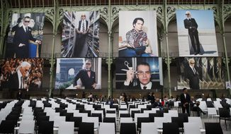 """Photographes of late German fashion designer Karl Lagerfeld are displayed for an event named """"Karl for Ever"""" at the Grand Palais in Paris, France, Thursday, June 20, 2019. The event pays tribute to late German fashion designer Karl Lagerfeld who died Feb. 19, 2019. (AP Photo/Francois Mori)"""