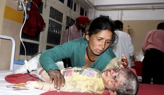 EDS NOTE: GRAPHIC CONTENT - A woman attends to her injured child receiving treatment at a hospital in Kullu, in the northern Indian state of Himachal Pradesh, Thursday, June 20, 2019. A bus fell into a deep gorge along a sharp curve on a mountainous road in northern India, killing more than 20, police said. Dozens more people were injured and hospitalized in Kullu, a town in Himachal Pradesh state, police officer Shalini Agnihotri said. (AP Photo/Aqil Khan)