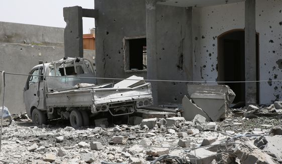 A vehicle and structure is damaged from fighting in the region of Tajoura , east of the Libyan capital Tripoli, Saturday, June 15, 2019.  Humanitarian workers remain deeply concerned about the safety and well-being of some 3,700 refugees and migrants in detention centers that are already exposed to, or are located close to, active fighting.  (AP Photo/Hamza Turkia, File)