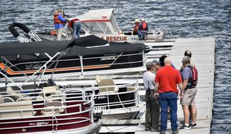 In this Monday, June 17, 2019 photo, emergency responders stage at the Yacht Basin marina east of Helena, Mont., as search and rescue teams search for a missing diver near Cemetery Island on Canyon Ferry Lake. Searchers have found the body of a scuba diver on Wednesday, June 19, 2019, who has been missing since Monday. (Thom Bridge/Independent Record via AP)