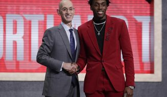 NBA Commissioner Adam Silver, left, poses for photographs with North Carolina's Nassir Little after the Portland Trail Blazers selected him with the 25th pick overall in the NBA basketball draft Thursday, June 20, 2019, in New York. (AP Photo/Julio Cortez)