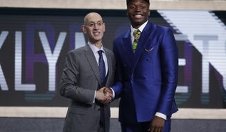 NBA Commissioner Adam Silver poses for photographs with Florida State's Mfiondu Kabengele after the Brooklyn Nets selected him as the 27th pick overall in the NBA basketball draft Thursday, June 20, 2019, in New York. (AP Photo/Julio Cortez)