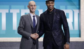 NBA Commissioner Adam Silver, left, poses for photographs with Kentucky's PJ Washington, after the Charlotte Hornets selected him as the 12th pick overall pick in the NBA basketball draft Thursday, June 20, 2019, in New York. (AP Photo/Julio Cortez)