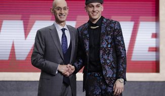NBA Commissioner Adam Silver, left, poses for photographs with Kentucky's Tyler Herro after the Miami Heat selected him as the 13th pick overall in the NBA basketball draft Thursday, June 20, 2019, in New York. (AP Photo/Julio Cortez)