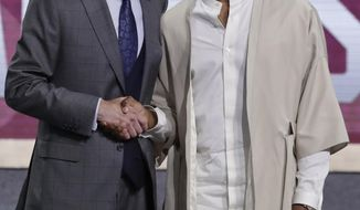 Vanderbilt's Darius Garland poses for photographs with NBA Commissioner Adam Silver after being selected with the fifth pick overall by the Cleveland Cavaliers in the NBA basketball draft Thursday, June 20, 2019, in New York. (AP Photo/Julio Cortez)