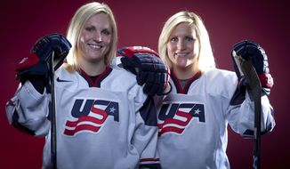 FILE - In this Oct. 2, 2013, file photo, United States Olympic Winter Games Hockey players Jocelyne Lamoureux, left, and Monique Lamoureux pose for a portrait at the Team USA Media Summit in Park City, Utah. A judge has thrown out a discrimination lawsuit by 11 former University of North Dakota women's hockey players seeking to have the program reinstated. School administrators cited budget woes when the program was dropped in the spring of 2017. The team reached the NCAA quarterfinals two straight years when twin sisters and U.S. Olympic stars Monique and Jocelyne Lamoureux were on the roster. (AP Photo/Carlo Allegri, File)