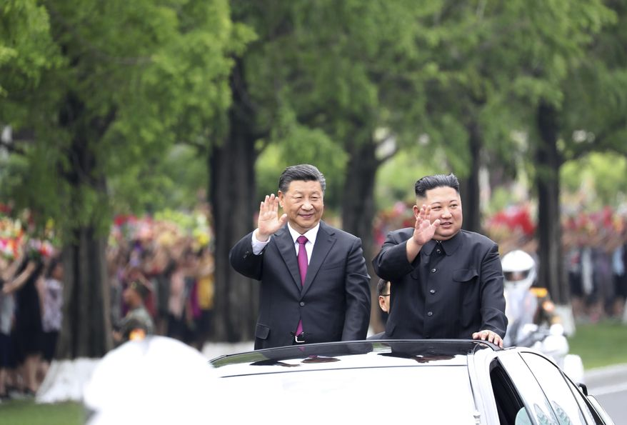 In this Thursday, June 20, 2019, photo released by China's Xinhua News Agency, visiting Chinese President Xi Jinping, left, and North Korean leader Kim Jong-un wave from an open top limousine as they travel along a street in Pyongyang, North Korea. (Ju Peng/Xinhua via AP)