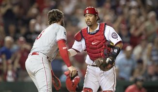 Washington Nationals catcher Kurt Suzuki extends a gesture to Philadelphia Phillies' Bryce Harper, a former National, after tagging him out during the fourth inning of a baseball game in Washington, Thursday, June 20, 2019. (AP Photo/Manuel Balce Ceneta) ** FILE **