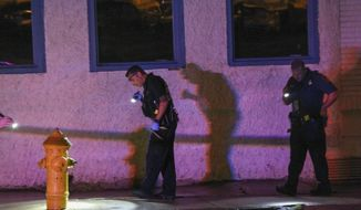 Police look for evidence early Thursday, June 20, 2019, in Allentown, Pa., following a shooting outside a nightclub.  The street shooting in eastern Pennsylvania that left 10 people wounded early Thursday is likely to be gang-related, authorities said. (Rich Rolen/The Morning Call via AP)