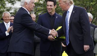 FILE - In this Monday, June 10, 2019, file photo, President Donald Trump shakes hands with racing team owner Roger Penske, left, as driver Simon Pagenaud watches on the South Lawn at the White House in Washington, as the president honored Team Penske for winning the 2019 Indianapolis 500 auto race. President Trump said Thursday, June 20, 2019, that he's awarding a Presidential Medal of Freedom to Penske, the most powerful man in American motorsports. (AP Photo/Patrick Semansky, File)