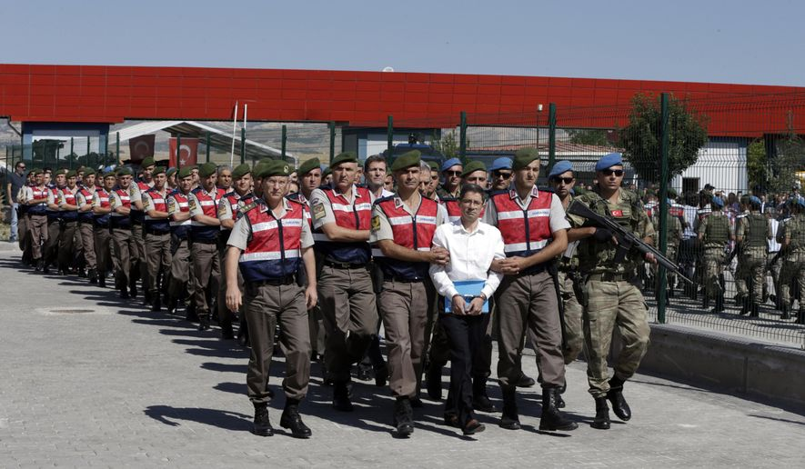 FILE - In this Aug. 1, 2017 file photo, paramilitary police and members of the special forces escort suspects of a failed coup in 2016, among them former Air Force commander Akin Ozturk, outside the courthouse at the start of a trial, in Ankara, Turkey. Turkey's state-run news agency says Thursday, June 20, 2019, a court in Ankara has sentenced several people, including Ozturk, accused of being the ringleaders of the 2016 failed military coup, to life terms in prison.(AP Photo/Burhan Ozbilici, File)