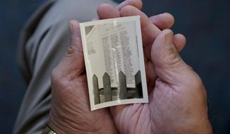 In this June 11, 2019 photo, Charlie Velazquez holds a photo that he inherited from his dad in San Ysidro, Calif. The wallet size photo is a photograph of the original plaque that displayed the 147 names of men and women from San Ysidro, Calif., who served in WWII, including the name so his two brothers, Alfredo and Adolfo who served in the U.S. Army. (Nelvin C. Cepeda/The San Diego Union-Tribune via AP)