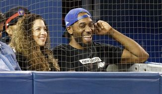 Toronto Raptors' Kawhi Leonard and his girlfriend, Kishele Shipley, watch the Toronto Blue Jays play the Los Angeles Angels during a baseball game Thursday, June 20, 2019, in Toronto. (Mark Blinch/The Canadian Press via AP)