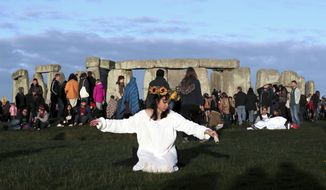 A reveler prays at sunrise as thousands gather at the ancient stone circle Stonehenge to celebrate the Summer Solstice, the longest day of the year, near Salisbury, England, Friday, June 21, 2019. (AP Photo/Aijaz Rahi)
