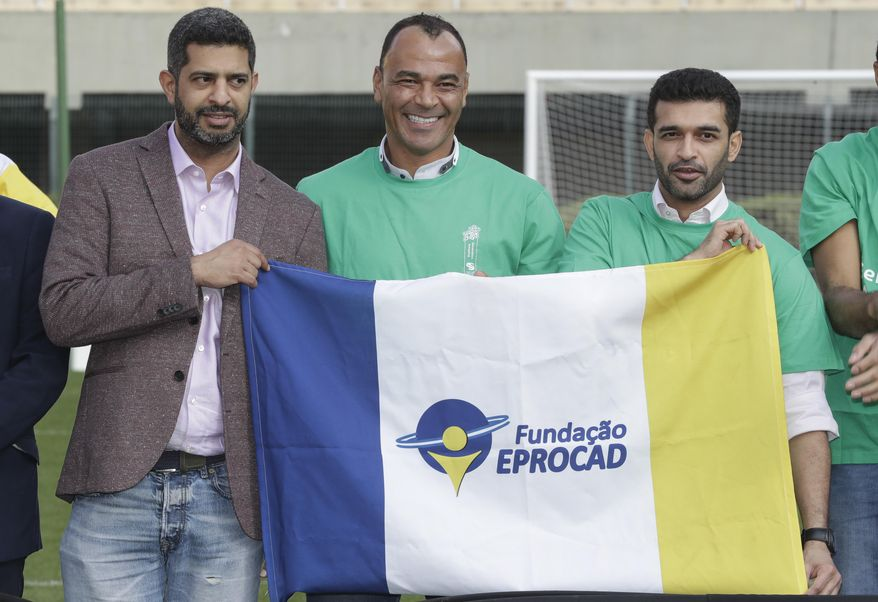Former Brazilian soccer player Cafu, center, poses for a photo with Hassan Al Thawadi, left, Chairman of the FIFA World Cup Qatar 2022, and Nasser Al-Khater, right, deputy-secretary general of the Qatar 2022 organizing committee, during a event where Cafu was presented as an Ambassador for the World Cup 2022, in Sao Paulo, Brazil, Friday, June 21, 2019. (AP Photo/Andre Penner)