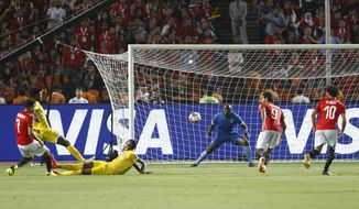 Egypt's Mahmoud Hassan, left, scores during the group A soccer match between Egypt and Zimbabwe at the Africa Cup of Nations at Cairo International Stadium in Cairo, Egypt, Friday, June 21, 2019. Egypt won 1-0. (AP Photo/Ariel Schalit)