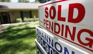 """This June 13, 2019, photo shows a house with a """"sold pending"""" sign fixed on the realtor's sign in northeast Jackson, Miss. On Friday, June 21, the National Association of Realtors reports on sales of existing homes in May. (AP Photo/Rogelio V. Solis)"""