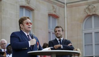 French President Emmanuel Macron, right, listens to Sir Elton John speaking in the presidential Elysee Palace in Paris, Friday, June 21, 2019. Sir Elton John received the Legion of Honor, France's highest award, during a visit to the presidential Elysee Palace (AP Photo/Lewis Joly, Pool)