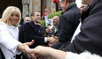 "FILE - In this May 26, 2019 file photo, French President Emmanuel Macron, center, and his wife Brigitte Macron shake hands to well-wishers after voting in the European elections in Le Touquet, northern France. In an unusually intimate radio interview, Brigitte Macron said her husband's 2017 election as president ""terrorized"" her and insisted that she has no political ambitions, and described the complexities of her relationship with a man 24 years her junior. (Ludovic Marin/Pool via AP, File)"