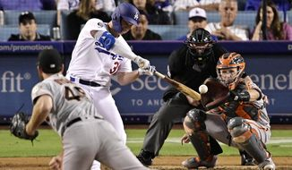 Los Angeles Dodgers' Joc Pederson hits a two-run home run off San Francisco Giants relief pitcher Sam Dyson, front, during the seventh inning of a baseball game Thursday, June 20, 2019, in Los Angeles. (AP Photo/Mark J. Terrill)