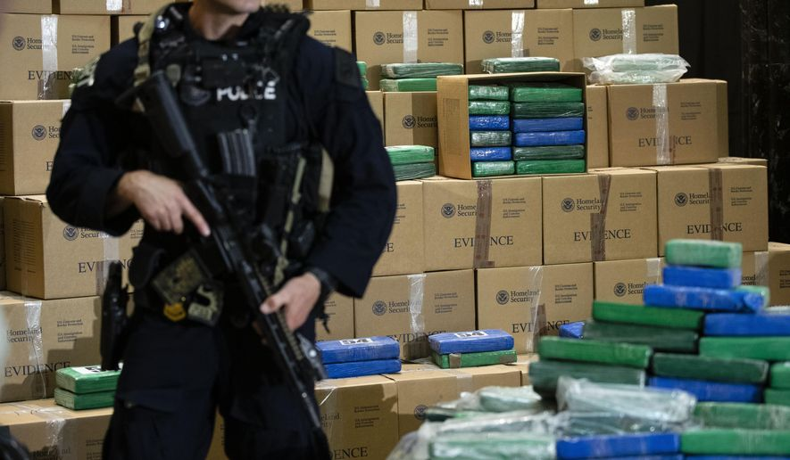 An officer stand guard over a fraction of the cocaine seized from a ship at a Philadelphia port that was displayed at a news conference at the U.S. Custom House in Philadelphia, Friday, June 21, 2019. Federal officials have estimated the seized drugs had a street value of more than $1 billion. (AP Photo/Matt Rourke)