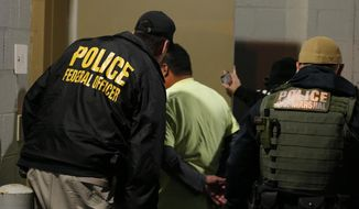 "In this Oct. 22, 2018, file photo U.S. Immigration and Customs Enforcement agents escort a target to lockup during a raid in Richmond, Va. On Friday, Nov. 15, 2019, immigration officials tied a third murder arrest in two months to sanctuary city policies in the Seattle, Washington, area, saying an illegal immigrant who was twice shielded from deportation by King County slew a man ""as he lay asleep in his own home.""  (AP Photo/Steve Helber, File)"