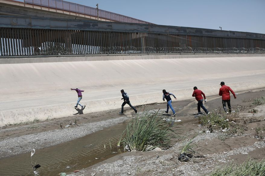 In this June 15, 2019, photo, migrants cross the Rio Bravo illegally to surrender to the American authorities, on the U.S.-Mexico border between Ciudad Juarez and El Paso. (Associated Press) **FILE**
