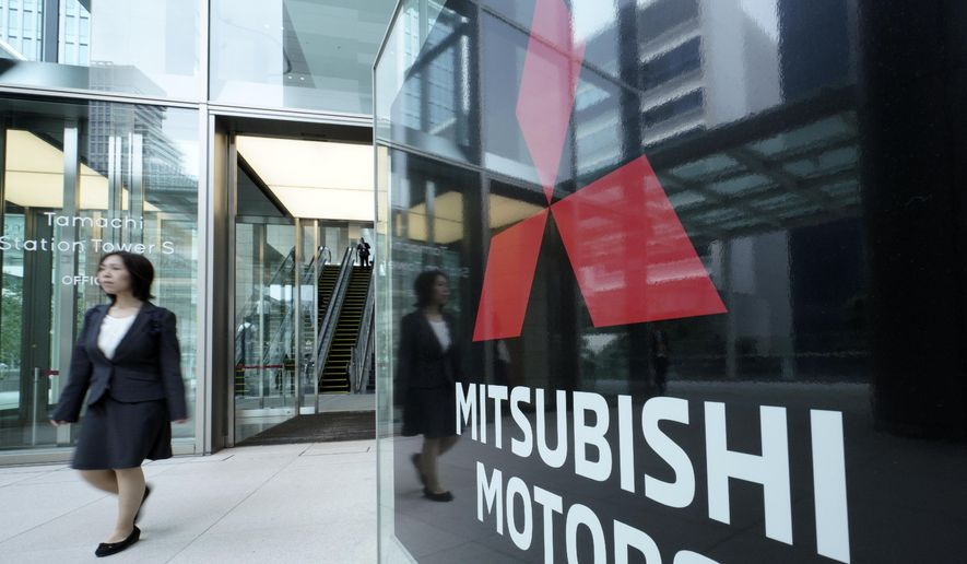 A woman walks past a sign of Mitsubishi Motors at its headquarter in Tokyo Friday, June 21, 2019. Mitsubishi Motors Corp. shareholders approved on Friday the ouster of Carlos Ghosn, who was pivotal in the Japanese automaker's three-way partnership with Nissan and Renault until he was arrested on financial misconduct charges last year. (AP Photo/Eugene Hoshiko)