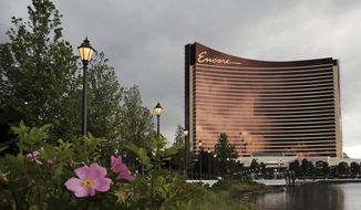 Beach Plum flowers bloom along the banks of the Mystic River in front of the Encore Boston Harbor casino in Everett, Mass., Friday, June 21, 2019.  The Wynn Resorts casino is scheduled to open to officially open to the public on Sunday, June 23rd. (AP Photo/Charles Krupa)