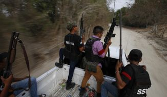Members of a FUPCEG vigilante group patrol in Xaltianguis, Guerrero state, Mexico, Wednesday, May 29, 2019. The heavily armed vigilante force took over the town in the Mexican state of Guerrero last month by driving out a rival band, blowing up a car with gas cylinders and cutting up the body of one of two fallen foes. (AP Photo/Rebecca Blackwell)