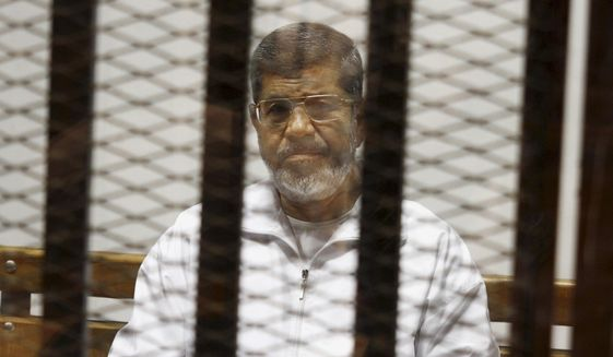 FILE - In this May 8, 2014 file photo, Egypt's ousted Islamist President Mohammed Morsi sits in a defendant cage in the Police Academy courthouse in Cairo, Egypt.  Morsi's collapse and death in a Cairo courtroom on June 17, 2019,  was a brief rallying point for the Muslim Brotherhood whose influence waned dramatically in the Middle East since the 2013 military coup in Egypt which had widespread public support at the time. The long-running enmity between the Brotherhood and most Sunni-led governments highlights the deep divisions among Sunni Muslims. It adds a further complication to the volatile region, where the split between Sunnis and Shiite Muslims has created rival camps.  (AP Photo/Tarek el-Gabbas, File)