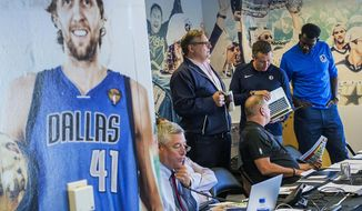 Dallas Mavericks president Donnie Nelson, standing left, meets in the draft room with assistant general manager Keith Grant, bottom left; director of player personnel Tony Ronzone, seated; vice president of basketball operations Michael Finley, standing right; and head athletic trainer Casey Smith, with laptop, Thursday, June 20, 2019, in Dallas, before the NBA basketball draft got underway in New York. (Smiley N. Pool/The Dallas Morning News via AP)