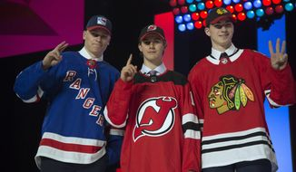 Top draft picks New York Rangers' Kaapo Kakko, New Jersey Devils' Jack Hughes and Chicago Blackhawks' Kirby Dach pose during the first round of the NHL hockey draft Friday, June 21, 2019, in Vancouver, British Columbia. (Jonathan Hayward/The Canadian Press via AP)