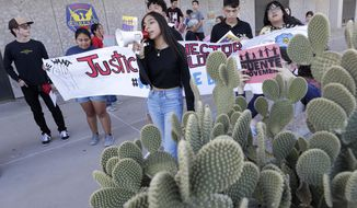 Protestors stand outside the Phoenix Police Department, Friday, June 21, 2019, in Phoenix. The family of Hector Lopez, who was shot dead in a confrontation with Phoenix police in May, has protested for information about what happened every week since then outside department headquarters, But as the Lopez family returned for the sixth weekly protest in a row, they're protesting a department bathed in a harsh national spotlight after the release of a videotaped encounter that showed police aiming guns and curses at a black couple whose young daughter took a doll from a store. (AP Photo/Matt York)